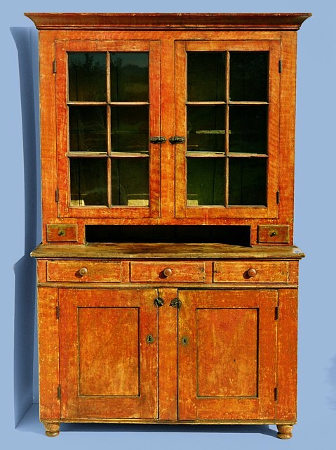PENNSYLVANIA DUTCH CUPBOARD IN BITTERSWEET ORANGE PAINT, WITH VINEAGR  DECORATION, ON TURNED FEET,