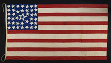 "39 STARS ON AN ANTIQUE AMERICAN FLAG WITH GREAT FOLK QUALITIES, CONSISTING OF A JUMBLED CONFIGURATION SURROUNDING A LARGE, HALOED CENTER STAR, SET AGAINST A ROYAL BLUE CANTON, THAT RESTS ON A RED STRIPE (SOMETIMES TERMED THE ""BLOOD STRIPE"" PR THE ""WAR STRIPE); PROBABLY MADE FOR THE 1876 CENTENNIAL OF AMERICAN INDEPENDENCE"