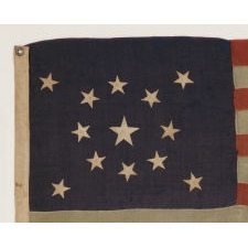 13 STARS IN A MEDALLION CONFIGURATION ON A SMALL-SCALE ANTIQUE AMERICAN FLAG OF THE 1890-1900 ERA, WITH AMPLE WEAR AND LOSSES
