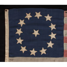 13 STARS IN A CIRCULAR VERSION OF THE 3RD MARYLAND PATTERN, ON A SMALL SCALE FLAG PROBABLY DATING TO THE FIRST HALF OF THE 1890'S, WITH ENDEARING PRESENTATION FROM EXTENDED USE