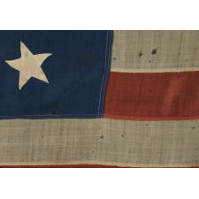 """13 HAND-SEWN STARS IN A 3-2-3-2-3 CONFIGURATION OF LINEAL ROWS, ON A LARGE SCALE ANTIQUE AMERICAN FLAG WITH A STENCILED SIGNATURE ALONG THE HOIST THAT READS """"GEO L. WRIGHT. BOYLSTON. MA."""", PROBABLY MADE FOR THE 100-YEAR ANNIVERSARY OF AMERICAN INDEPENDENCE IN 1876"""