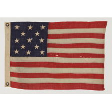 13 STARS ARRANGED IN A 3-2-3-2-3 LINEAL CONFIGURATION ON AN TINY ANTIQUE AMERICAN FLAG AMONG ITS COUNTERPARTS WITH PIECED-AND-SEWN CONSTRUCTION, ca 1895-1920's, MADE BY ANNIN IN NEW YORK CITY