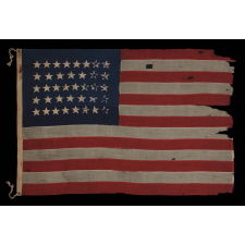 38 HAND-SEWN STARS IN A CONFINED PATTERN OF JUSTIFIED ROWS, ON AN ANTIQUE AMERICAN FLAG WITH ENDEARING WEAR AND WONDERUL PRESENTAITION, 1876-1889, COLORADO STATEHOOD