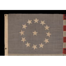 13 STARS IN A CIRCULAR VERSION OF THE 3RD MARYLAND PATTERN, ON A SMALL SCALE FLAG MADE IN THE PERIOD BETWEEN ROUGHLY 1885 AND 1895, WITH A DUSTY BLUE CANTON AND WITH STRIKING VISUAL PRESENTATION FROM LONG-TERM USE